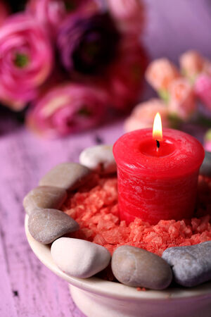 Composition with spa stones, candle  and flowers on color wooden table, on light background photo