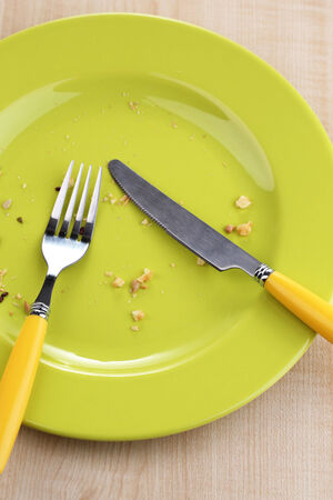 Plate with crumbs on wooden background  photo