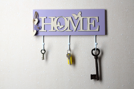 Keys hanging from hooks, on light wall background