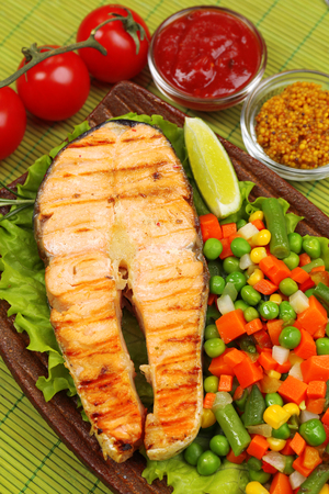 Tasty grilled salmon with vegetables, on bamboo mat photo
