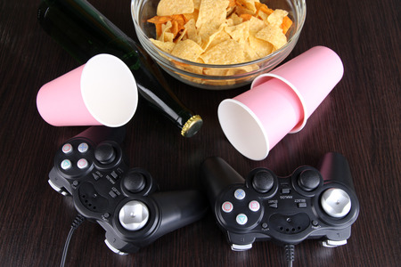 Black game controllers and bowl with snacks on wooden background photo