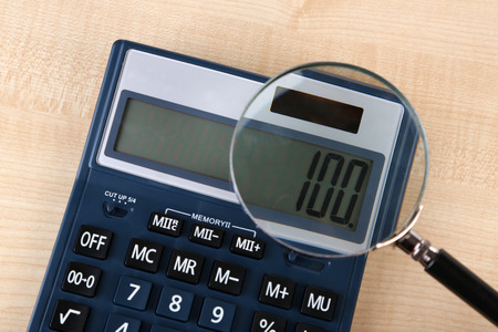 balanced budget: Fraud concept with magnifier and calculator, on wooden background