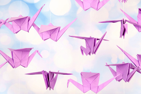 Origami cranes on light background photo