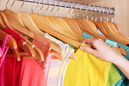 Colorful clothes hanging in wardrobe photo