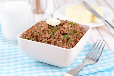 Boiled buckwheat in bowl on table close-up photo