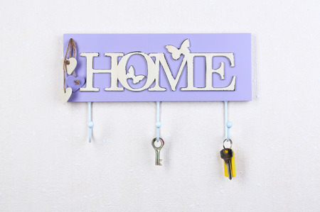 Keys hanging from hooks, on light wall background photo