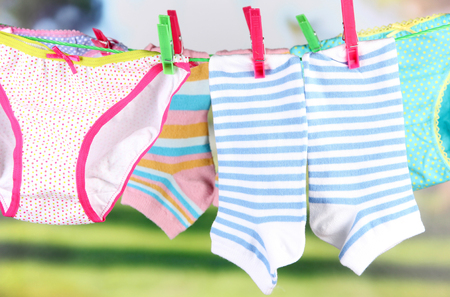 Baby clothes hanging on clothesline, on bright background photo