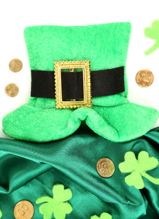 coins shot in golden color: Saint Patrick day hat with clover leaves and golden coins, isolated on white Stock Photo