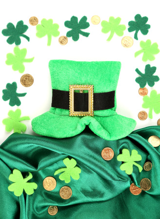 Saint Patrick day hat with clover leaves and golden coins, isolated on white photo