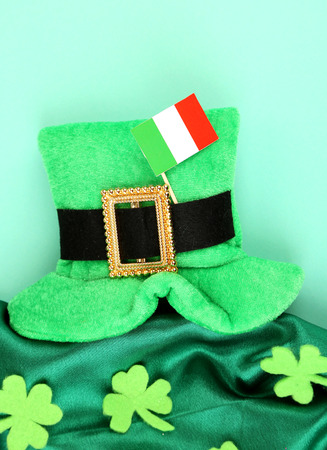 Saint Patrick day hat with clover leaves and Irish flag on green background photo