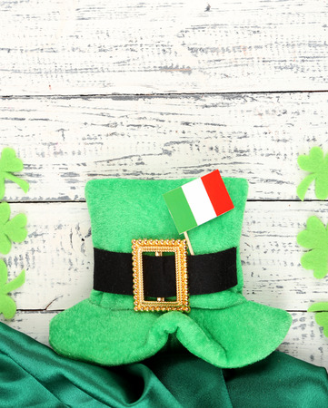 Saint Patrick day hat with clover leaves and Irish flag on wooden background photo