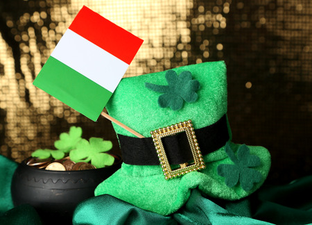 Saint Patrick day hat, pot of gold coins and Irish flag on shiny background photo