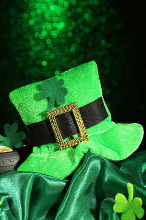 Saint Patrick day hat and pot of gold coins on green shiny background photo