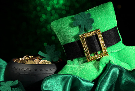 Saint Patrick day hat and pot of gold coins on green shiny background Stock Photo