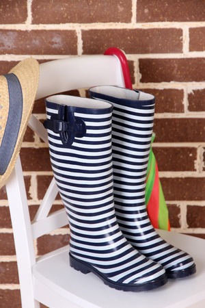Pair of colorful gumboots on chair on color wall background photo
