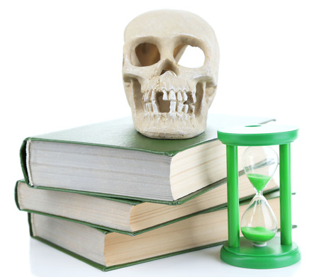 Hourglass and skull on old book isolated on white photo