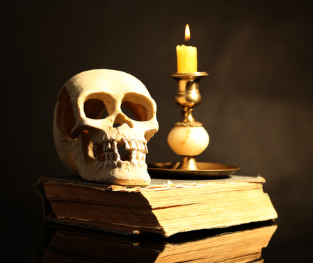 Skull and candle on old book  on dark color background photo
