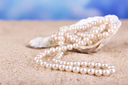Beautiful pearls in shell on sand, close up