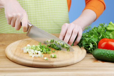 Female hands chopping onion on wooden board, close-up, on blue background photo