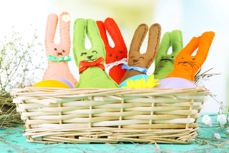 Funny handmade Easter rabbits in wicker basket photo