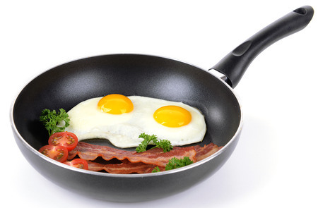 Scrambled eggs and bacon on frying pan isolated on white photo