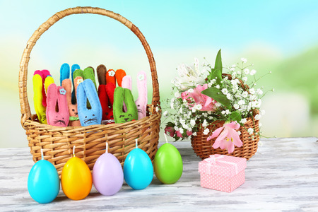Composition with funny handmade Easter rabbits in wicker basket photo