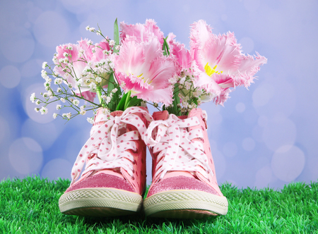 Beautiful gumshoes with flowers inside on green grass, on bright background photo