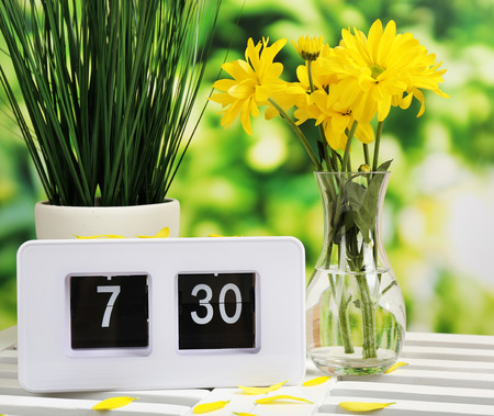 Digital alarm clock on table, on nature background photo