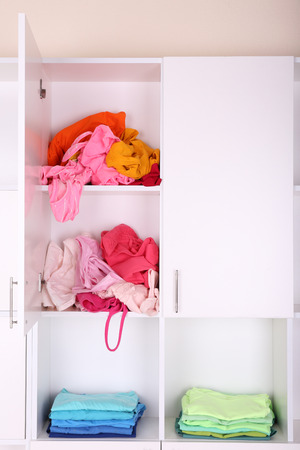 White shelves with colored clothing close up photo