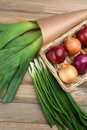close up of onions in a basket: Different raw onion on wooden background Stock Photo