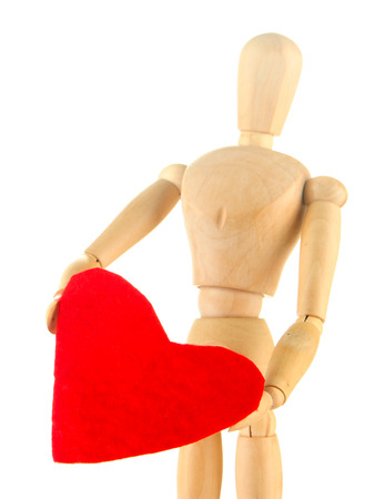 Wooden mannequin holding big red heart isolated on white photo