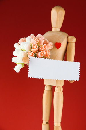 Wooden mannequin holding blank label and bouquet on red background photo
