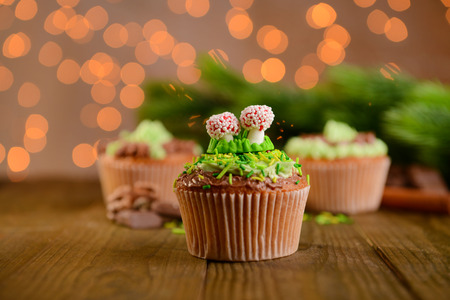 Tasty cupcakes with butter cream, on  wooden table, on bright background photo