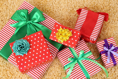 Many colorful presents with luxury ribbons  on color carpet background photo