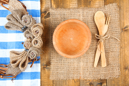 Rustic table setting with plate, fork and spoon, on wooden table photo