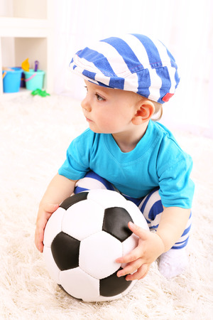 Cute little boy with football in room Stock Photo