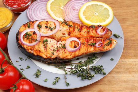Tasty grilled salmon with vegetables, on wooden table photo