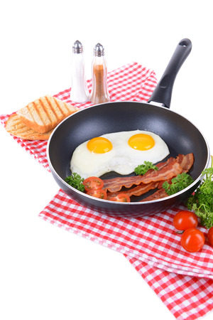 Scrambled eggs and bacon on frying pan on table close-up photo