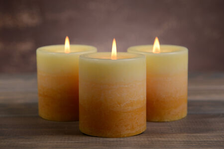 Beautiful candles on table on brown background photo