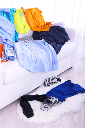 Messy colorful male clothing on  sofa on light background photo