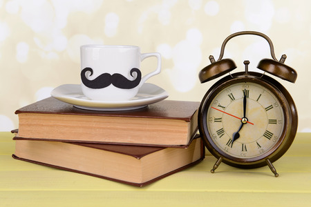 Cup with mustache on table on light background photo