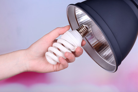 Hand changing light bulb for lamp at home photo