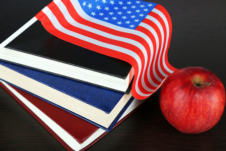 Composition of  American flag, books and apple  on wooden table background photo