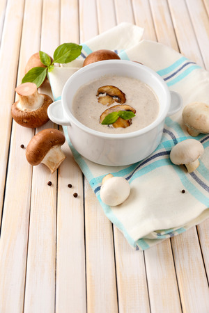 Mushroom soup in white pot, on napkin, on wooden background Stock Photo - 28053784