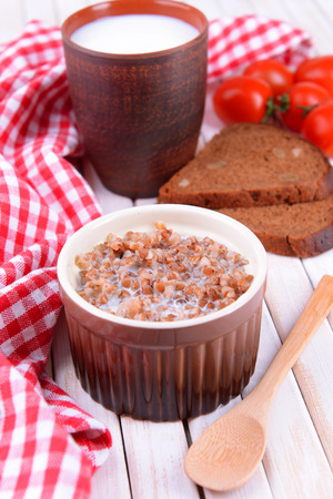 Boiled buckwheat with milk in bowl on table close-up photo