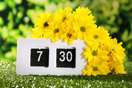 Digital alarm clock on green grass, on nature background photo