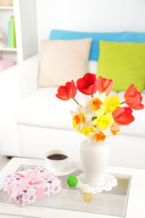 Beautiful spring flowers in vase on home interior background photo