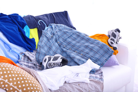 disorganized: Messy colorful male clothing on  sofa on light background
