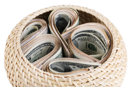 Packs of dollars stored in basket isolated on white