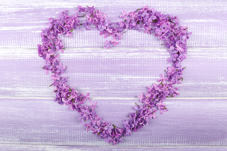 Beautiful lilac flowers in shape of heart on wooden background Stock Photo